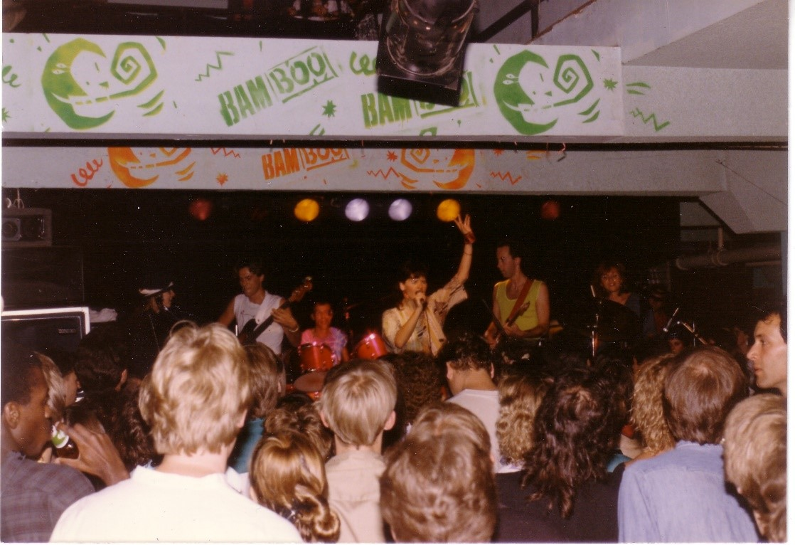A colour photograph of a crowd gathered to watch a performance of the Parachute Club on stage at the BamBoo. Lorraine Segato stands in the middle of the stage with her left arm raised and her right hand on a microphone, singing. Behind her musicians play.