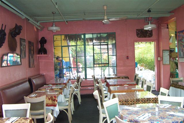 A photo of the interior of a restaurant featuring pink walls and white tables and chairs.