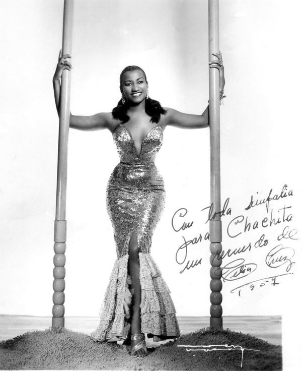 """Celia Cruz stands between two posts in a photography studio dressed in a shimmery strapless mermaid-style dress. She looks and smiles at the camera with each hand holding one of the posts. A handwritten notes on the photo reads """"Con toda simpatia para Chachita un recuerdo de Celia Cruz 1957"""""""