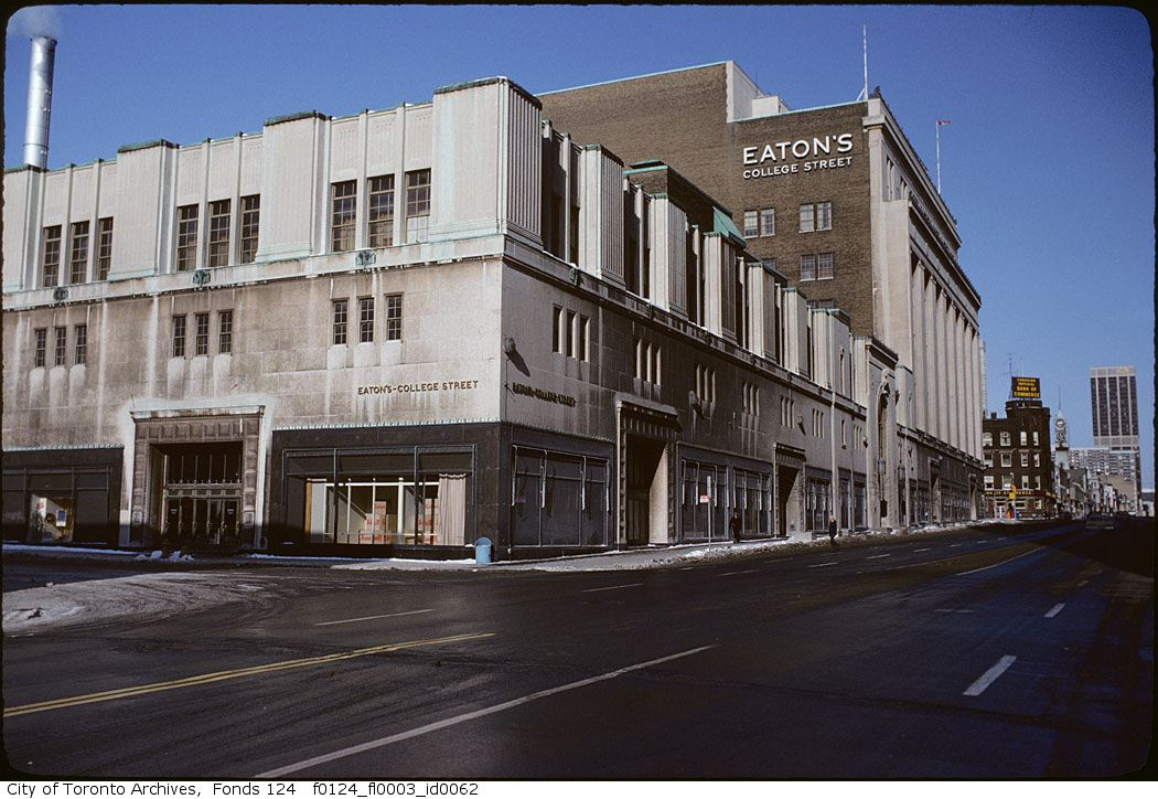 """A southwest view of the intersection of Yonge and College Streets in Toronto, focused on the Eaton's College Street location. In the background, there is a sign that says """"Eaton's College Street."""""""