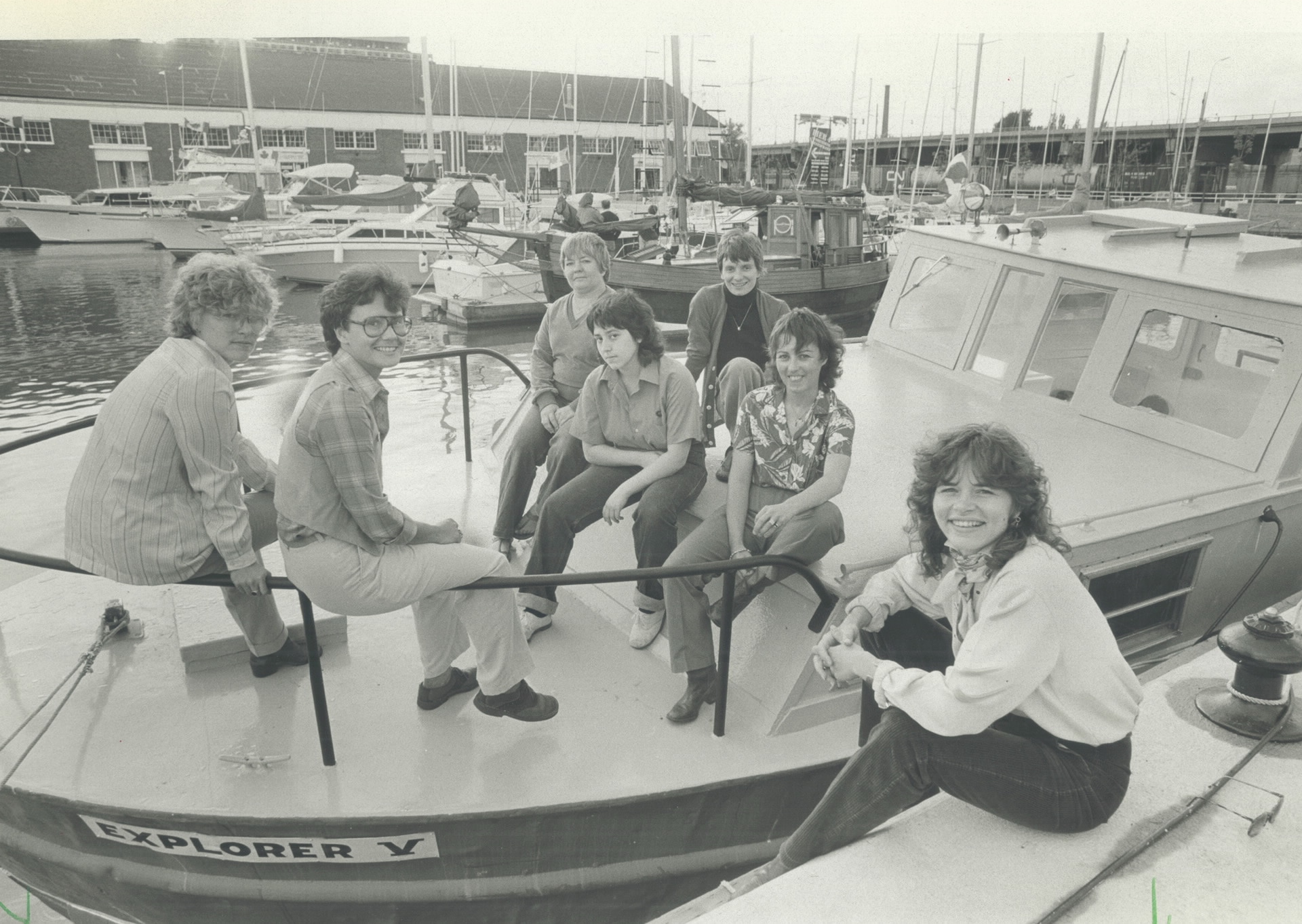 Six people sit on a boat that is moored in the Toronto harbour, with Lorraine Segato sitting in the foreground on the dock next to the boat.