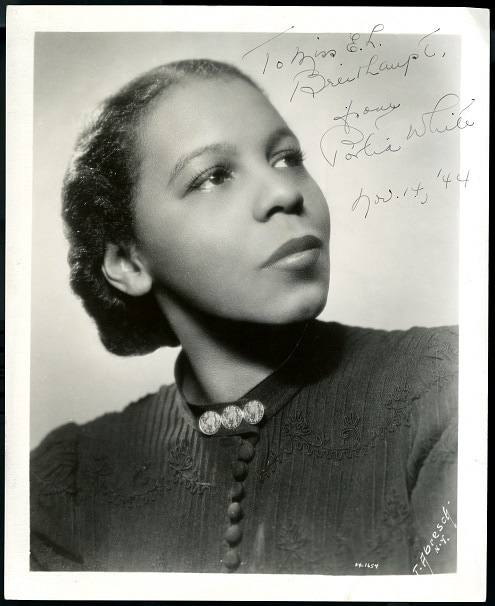 """Portrait of a Black woman looking up and to the left of the camera. Her hair is pulled back and she is wearing a dark blouse with three buttons at the collar. It is signed: """"To Miss E. L. Breithaupt. From Portia White. November 14, 44"""""""