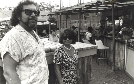 A black and white photograph of a man and a woman looking at the camera. The man wears a Hawaiian shirt and sunglasses. The woman wears a floral dress and sunglasses. They stand on an outside patio of a restaurant.