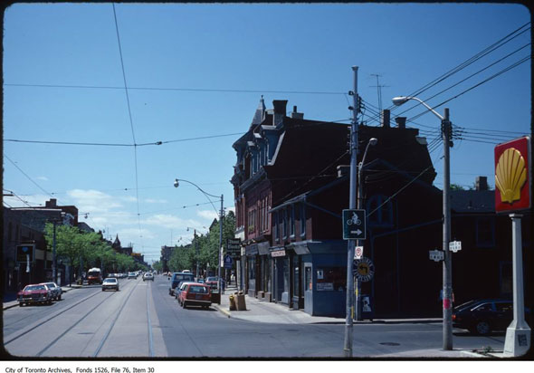 A colour photograph looking west along an intersection at Queen Street West and Beverley Street on a sunny June day in 1981.