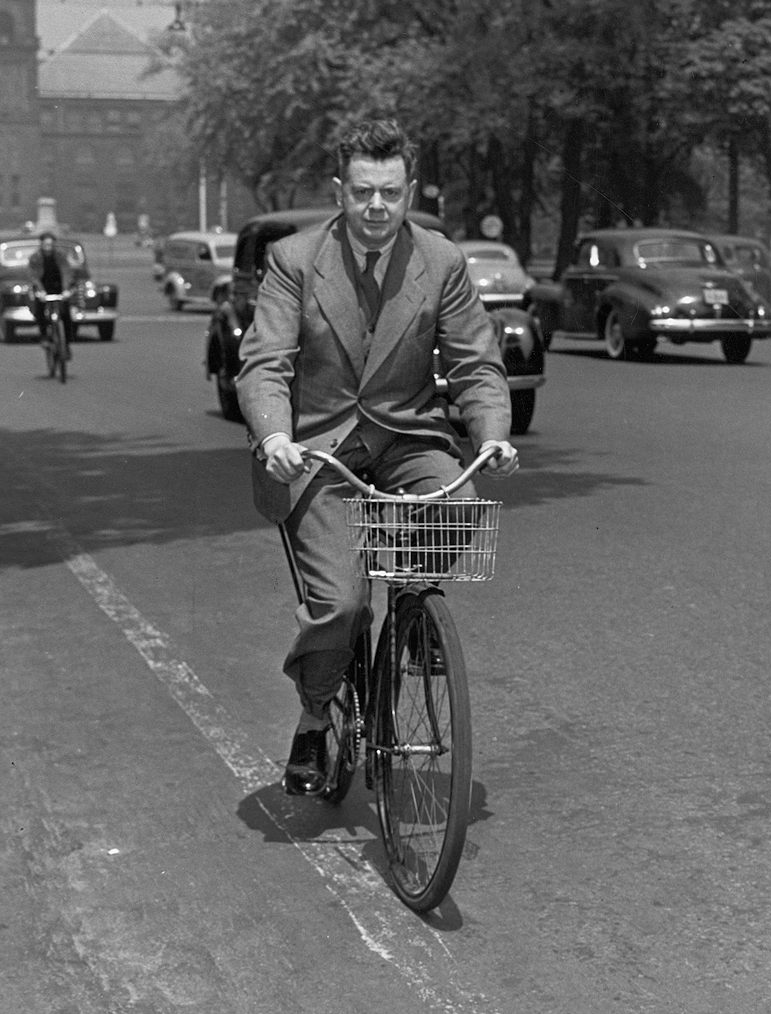 A man with a short haircut, wearing a long trenchcoat rides a bicycle down a major road. Cars can be seen behind him. He is looking at the camera.