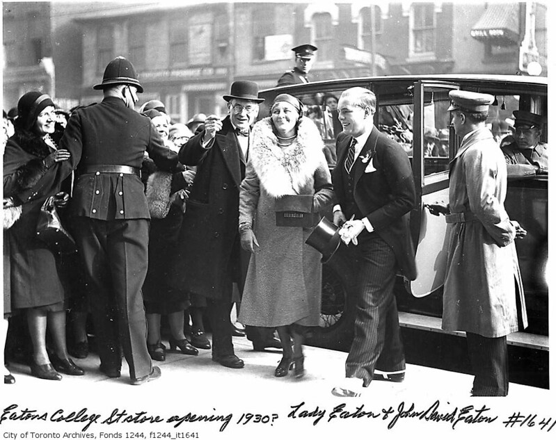 A woman in a fur coat and a man in a suit holding a top hat exit a car, with the door held open by the driver. They are surrounded by a crowd, held back by a policeman.