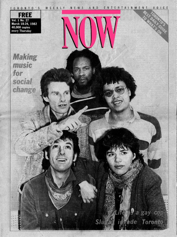 A black and white cover of NOW Magazine, featuring five individuals, including members of the band V, including Mohaj, Billy Bryans, and Lorraine Segato. The group is arrange with two people in the front; two behind, and one at the far back of the photograph. Billy Bryans, in the top left of the photo, is pointing to something with his right hand.
