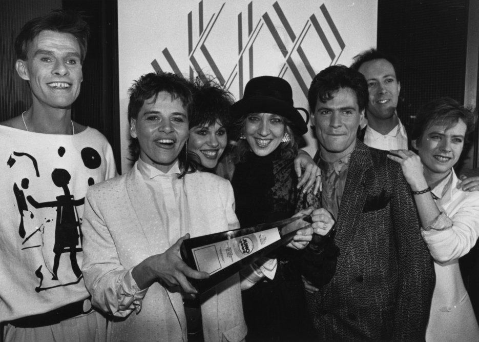 A black and white photo featuring seven people holding a JUNO award.
