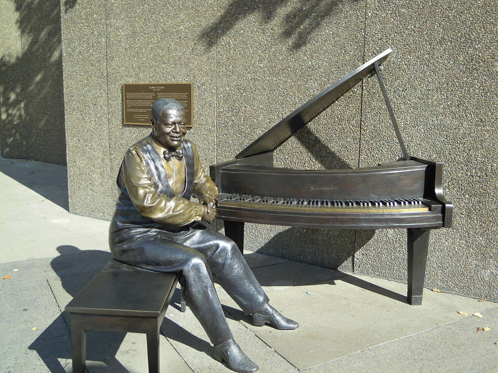 A colour photograph of a bronze statue depicting Oscar Peterson sitting at a piano.