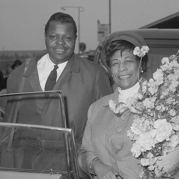 Oscar Peterson and Ella Fitzgerald stand side by side in a black and white photograph. Ella holds a bouquet of flowers.