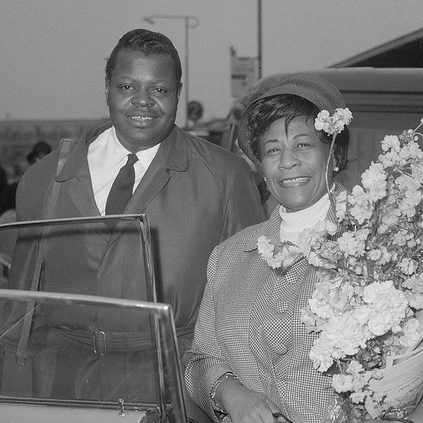 OscarPeterson et EllaFitzgerald se tiennent côte à côte dans une photographie en noir et blanc. Ella tient un bouquet de fleurs.