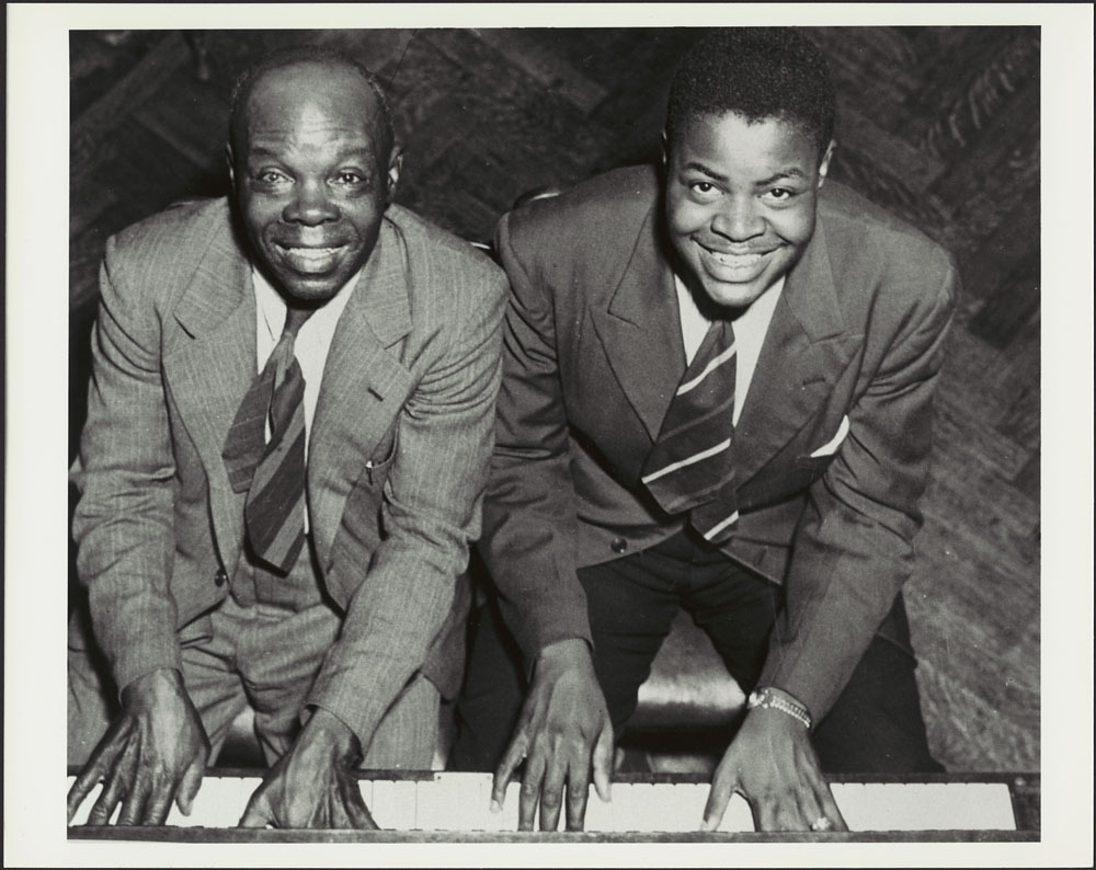 Black and white photograph of two black men - one older, and one in his late teens- both dressed in suits sitting at a piano looking up at the camera as their hands are placed side by side on the white ivory piano keys.