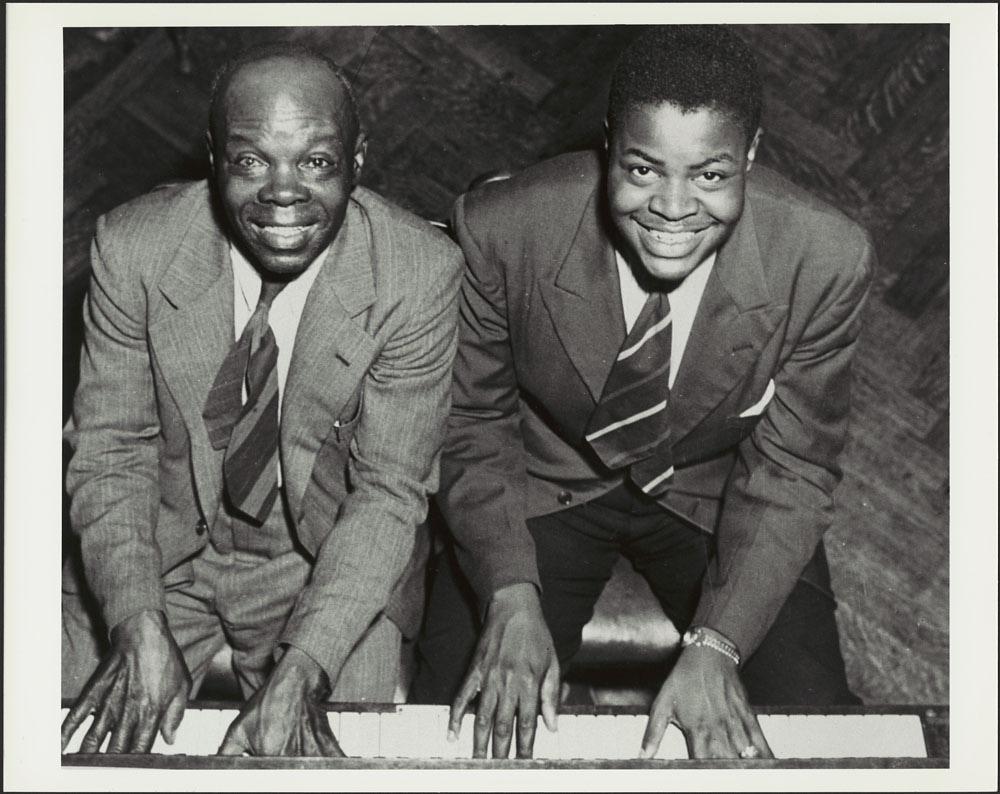 Photographie en noir et blanc de deux hommes noirs, l'un plus âgé et l'autre à la fin de son adolescence. Les deux portent un complet et sont assis à un piano. Ils regardent l'appareil photo, leurs mains placées côte à côte sur les touches blanches du piano.