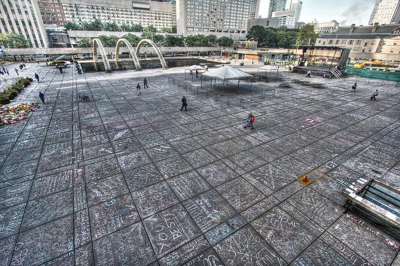 A colour photo of a large cement square, Nathan Phillips Square, with hundreds of multi-coloured chalk messages.
