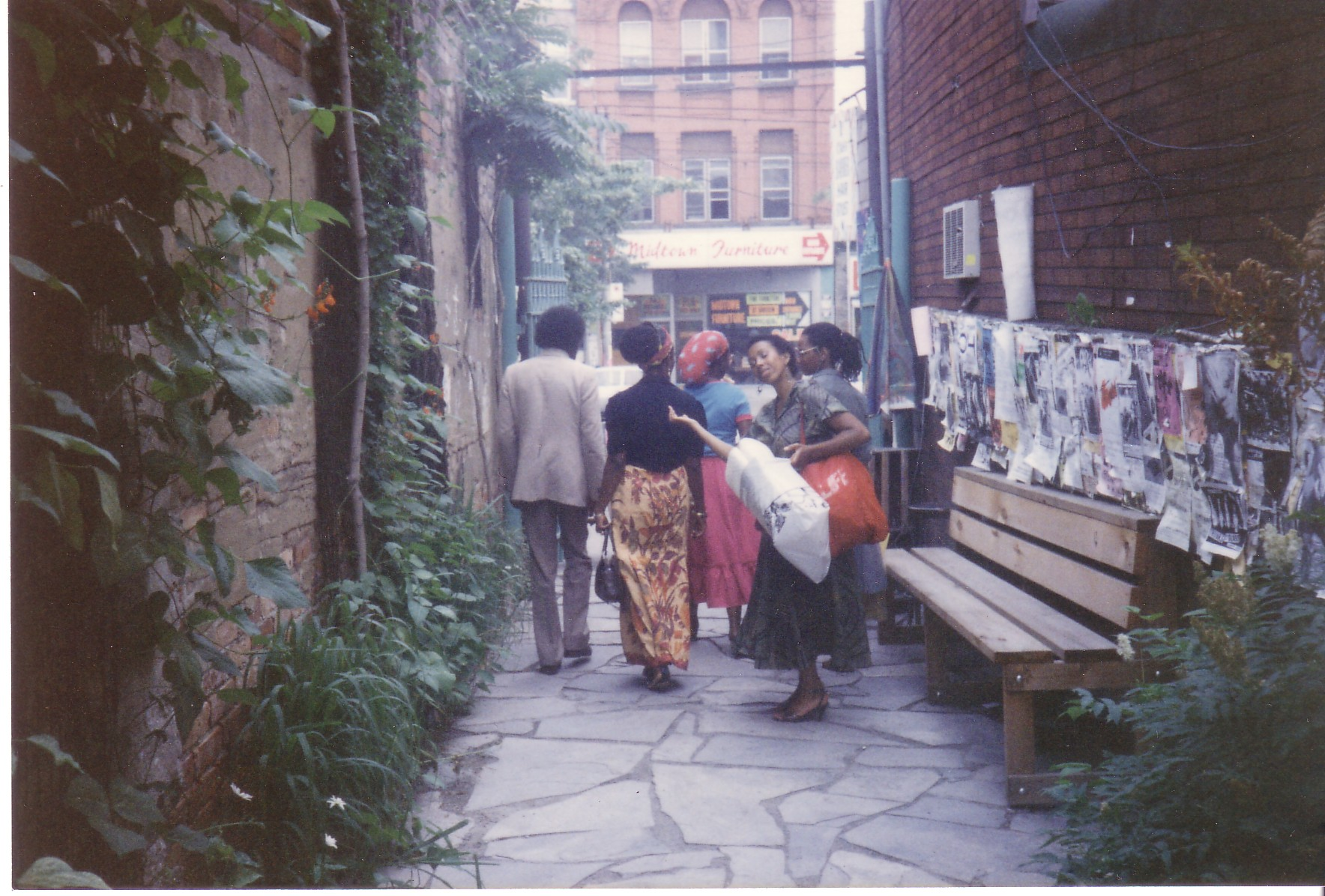 A colour photograph of an alley in which six people are walking away from the camera. One woman who is holding a white bag is turning back to look and smile at the camera.