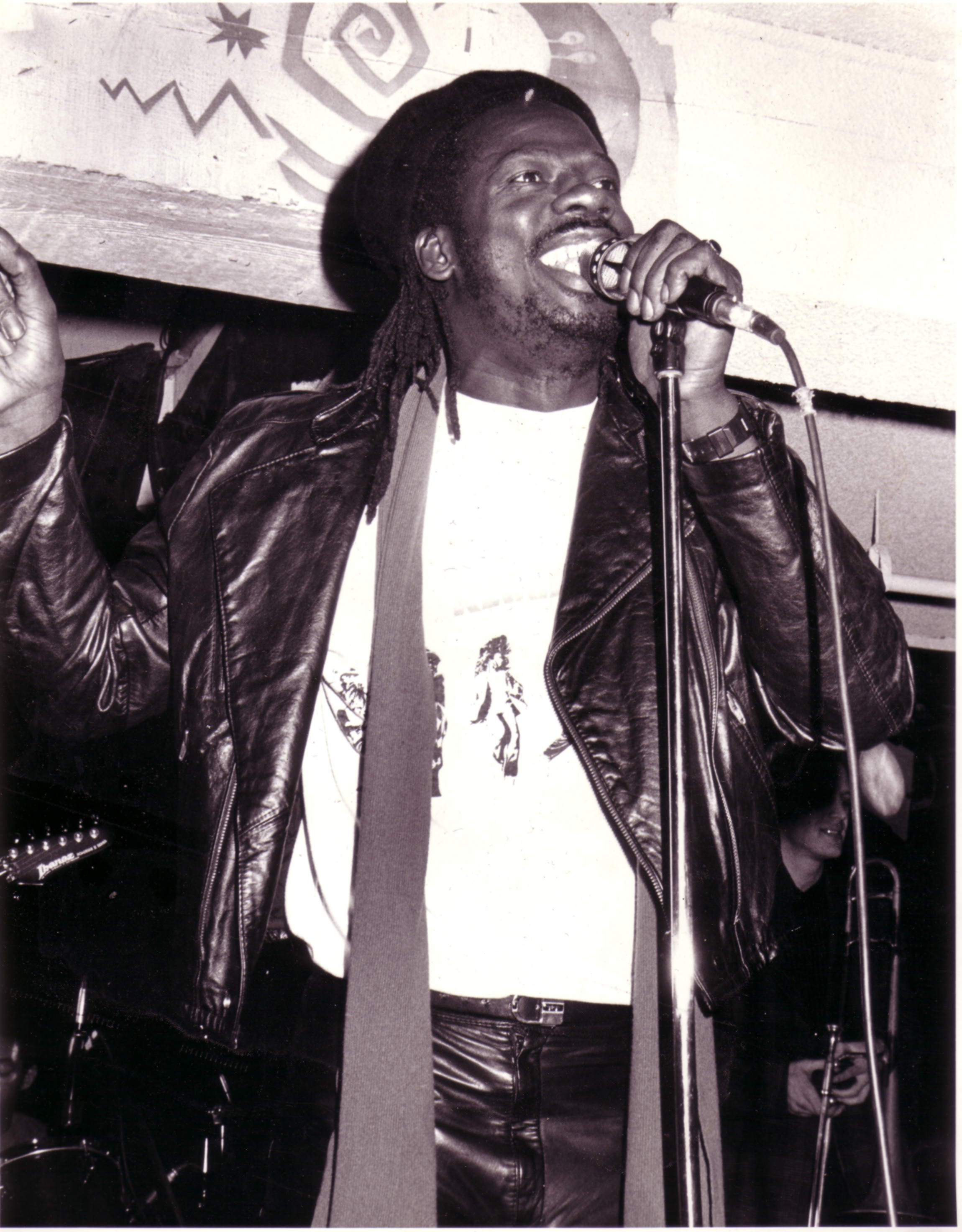 A black and white photo of a man on stage singing while holding a microphone