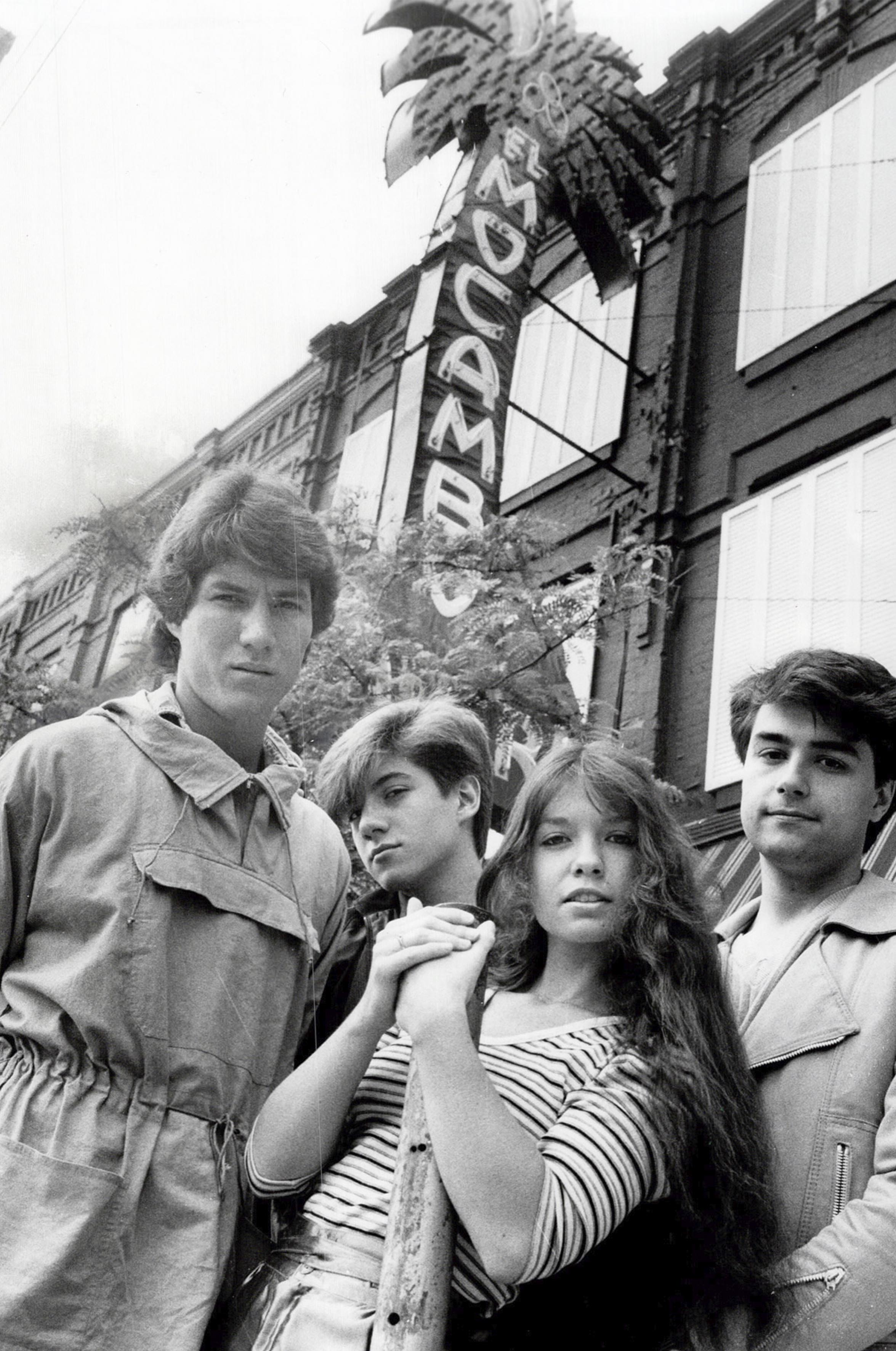 "A group of four young people stand in front of a music venue. Behind them the neon sign for the venue features a palm tree and the words ""El Mocambo""."
