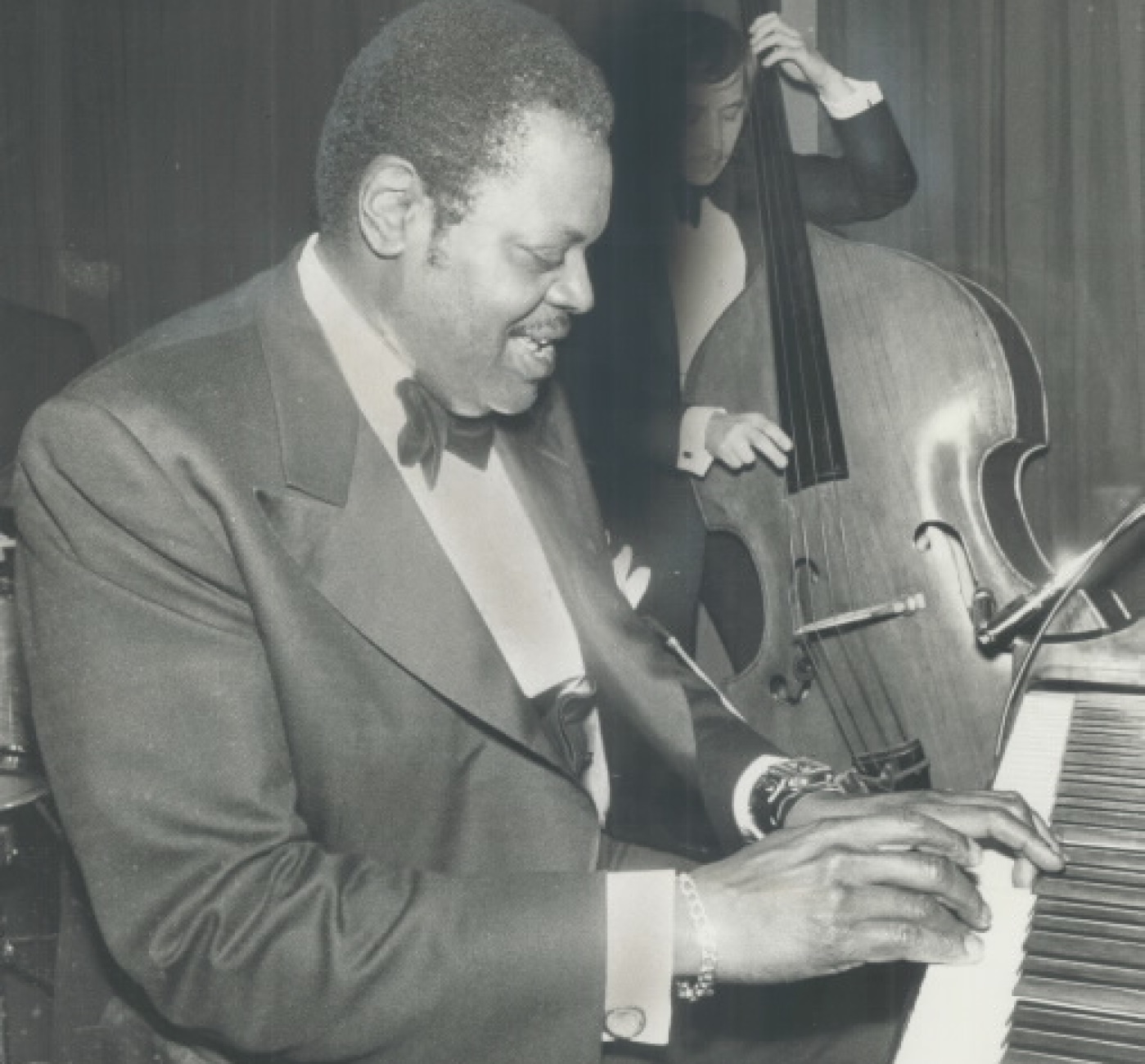 A man in a suit plays the piano. Behind him, a bassist plays.