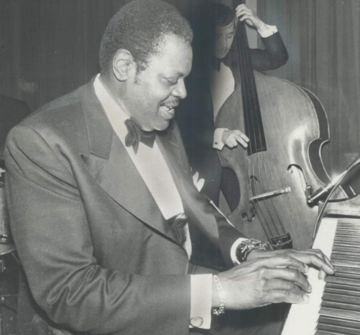 Un homme en complet joue du piano. Derrière lui, un contrebassiste joue.
