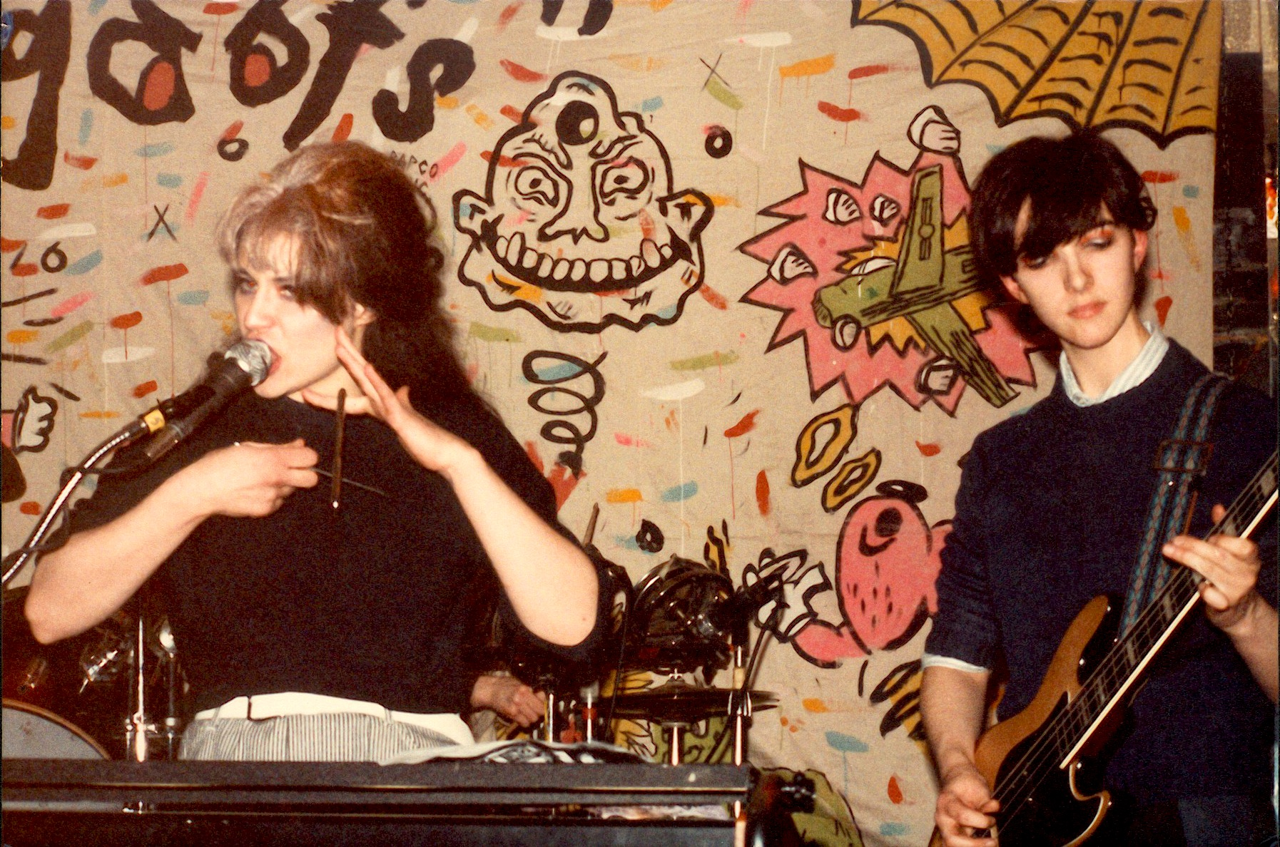 Two women on stage playing music in front of a painted backdrop. The left woman sings into a microphone and is sitting in front of a keyboard. The woman on the right plays a guitar.