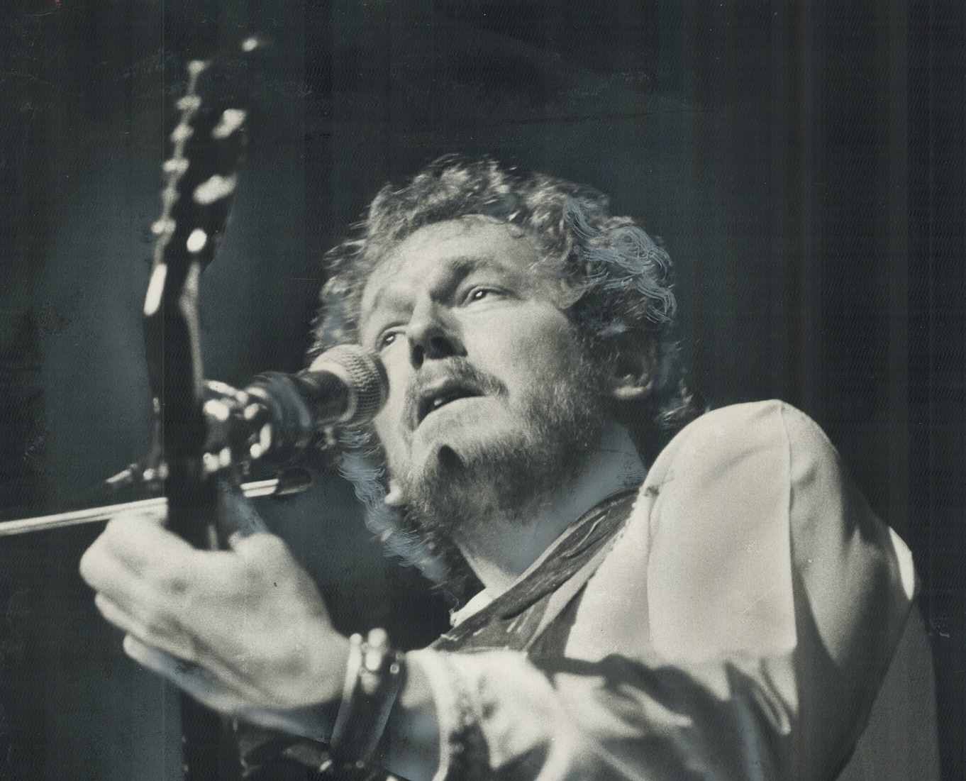 A man with wavy hair and a light beard plays guitar and sings into a microphone.