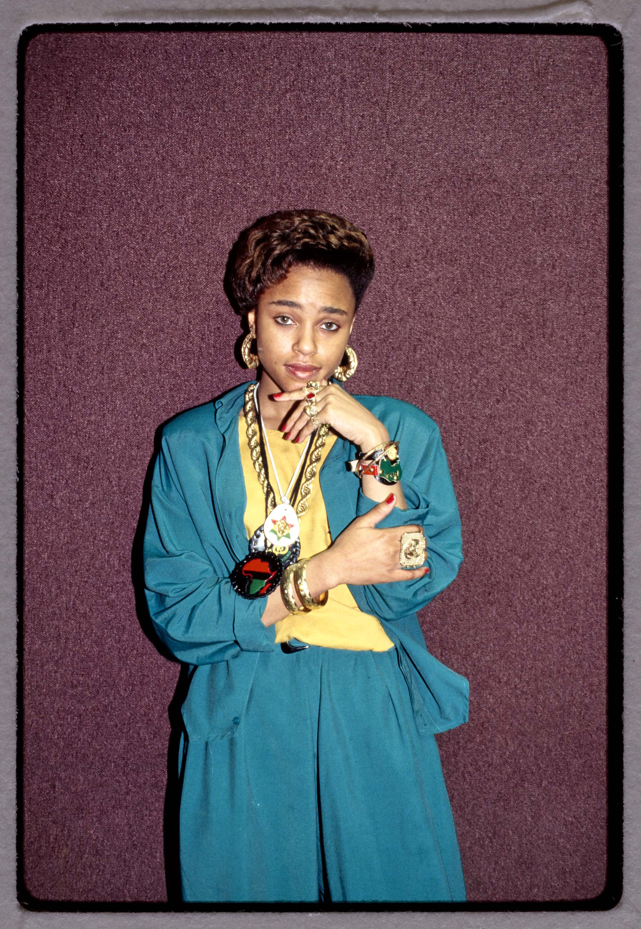 A young woman in a teal jacket and pants with a yellow shirt leans against a dark red backdrop. She has her left hand resting under her chin. She wears large gold earrings and a prominent necklace.