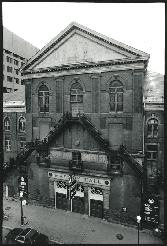 An exterior black and white photo of the front facade of Massey Hall, a three-story brick building with external fire escapes on the front.