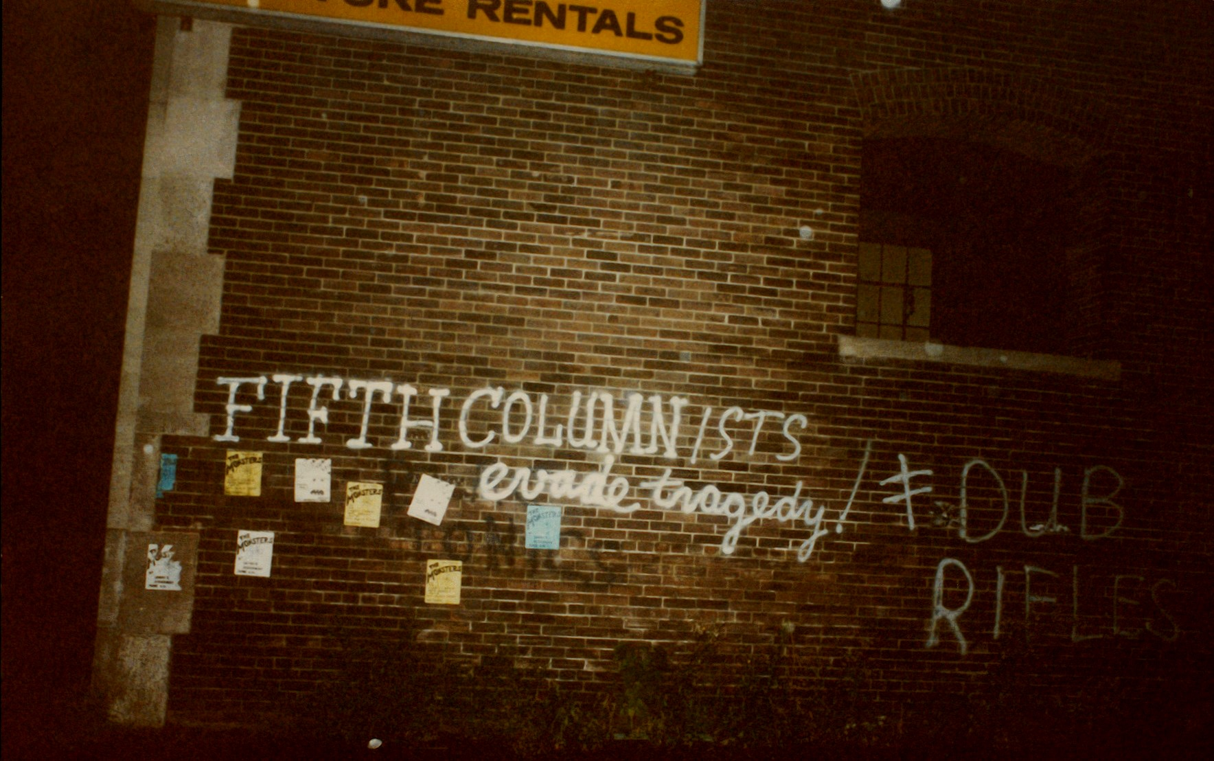 """A colour photo of a brick wall with the words """"Fifth Columnists evade tragedy"""" written on it in spray paint."""