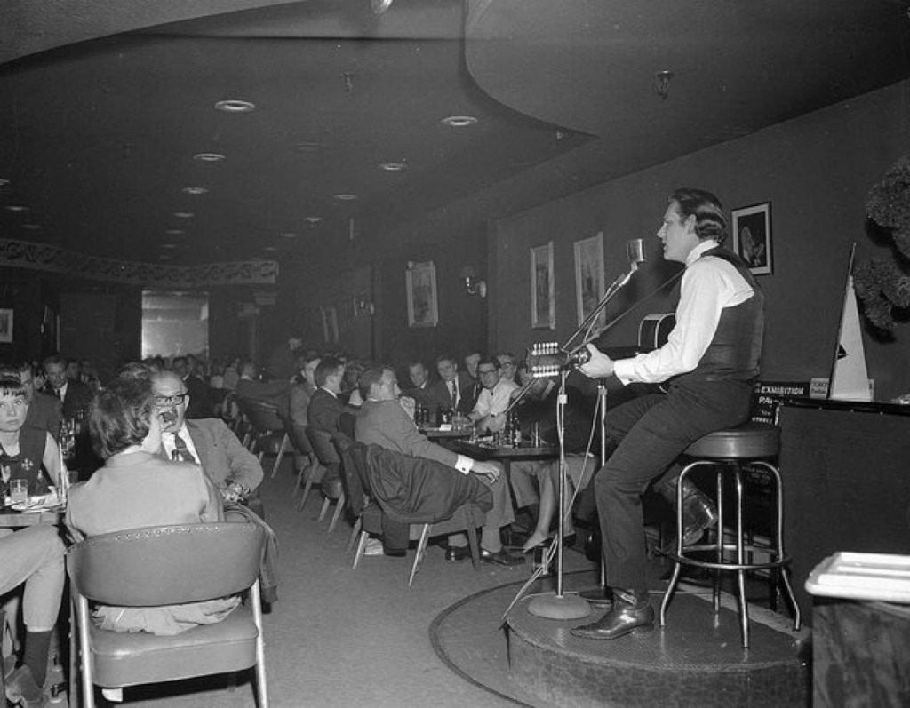 A man sits on a barstool on a raised platform at the right of the frame, holding a guitar and singing into a microphone. He sits in a crowded room, where the patrons are seated at four-top tables. In the front left of the frame, a man raises a glass to drink.