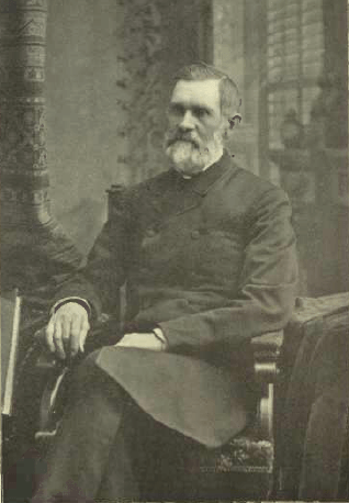 Bearded middle aged man sits in a black and white portrait wearing a double breasted knee length jacket, with his legs crossed and one hand in his lap, the other resting on the arm of the chair.