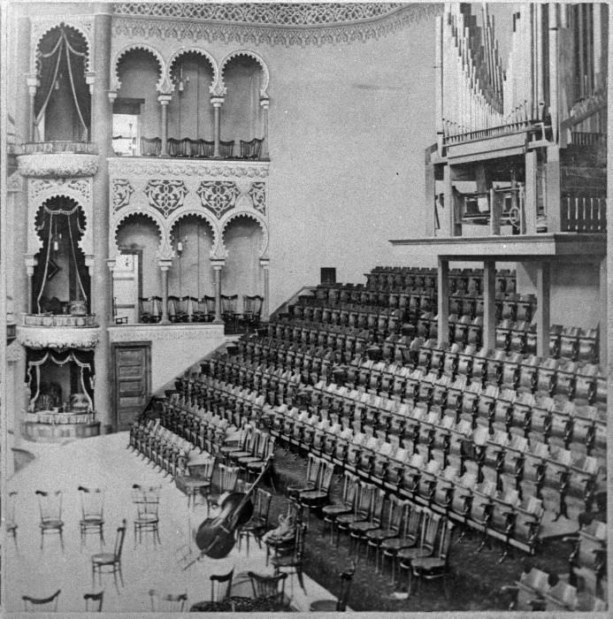 An interior of a concert hall, showing stadium-style theatre seats as well as balconies and hallways decorated with arches in a Moorish, arched style.