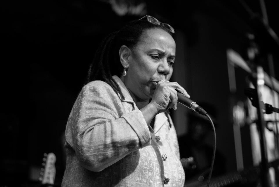 A black and white photograph of a woman who holds a microphone close to her mouth.
