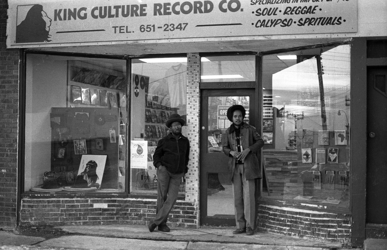 A black and white photograph of two men standing outside of a record store.