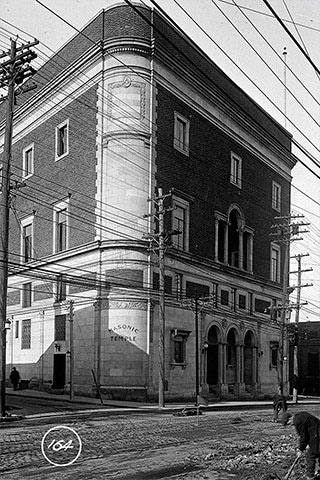 A black and white image of the exterior of a three-story building alongside a dirt-paved road.