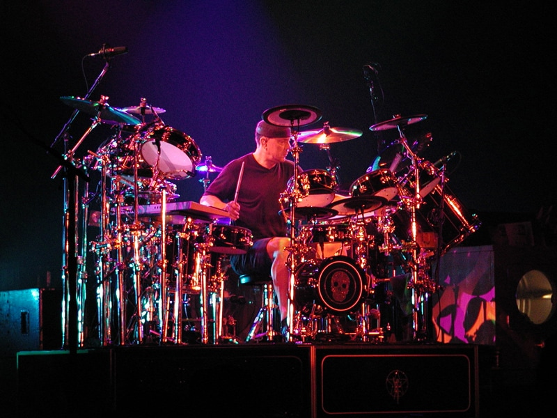 Neil Peart sits at a drum kit on stage.