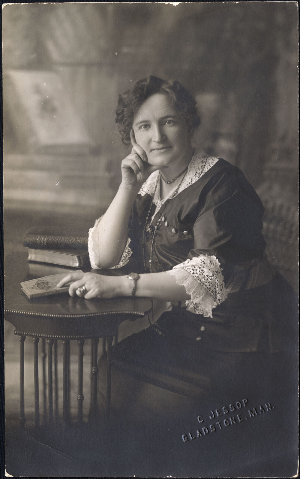 A photo portrait of a woman seated at a small table. She looks directly at the camera. Her left hand holds a piece of paper while her right hand rests under her chin and on the right side of her face. She wears a dark dress with white lace on the neckline and cuffs.