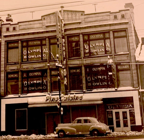 """An exterior photo of 333 Yonge Street. A three-story building advertises Olympia Bowling on the top two floors. On the ground floor a sign reads """"Fine Cuisine"""". An exterior horizontal sign reads """"Le Coq d'Or""""."""