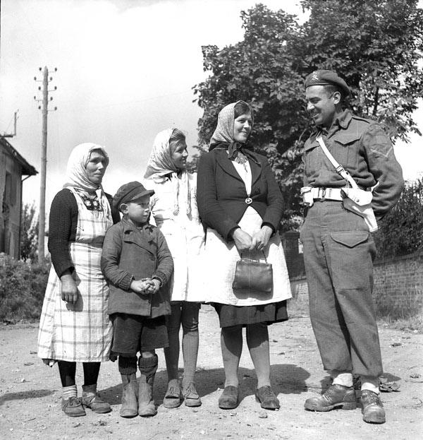 Une image en noir et blanc de deux femmes et d'un jeune garçon parlant à un homme en uniforme militaire.