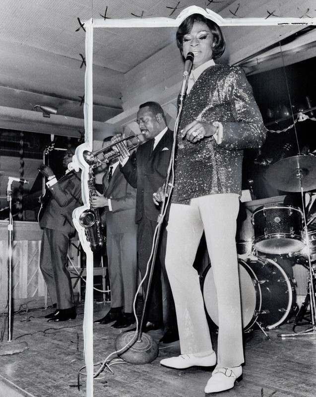 A singer in white pants and sequinned jacket holds a microphone on stage. A trumpet and saxophone player stand next to them. Behind them is a drum kit.