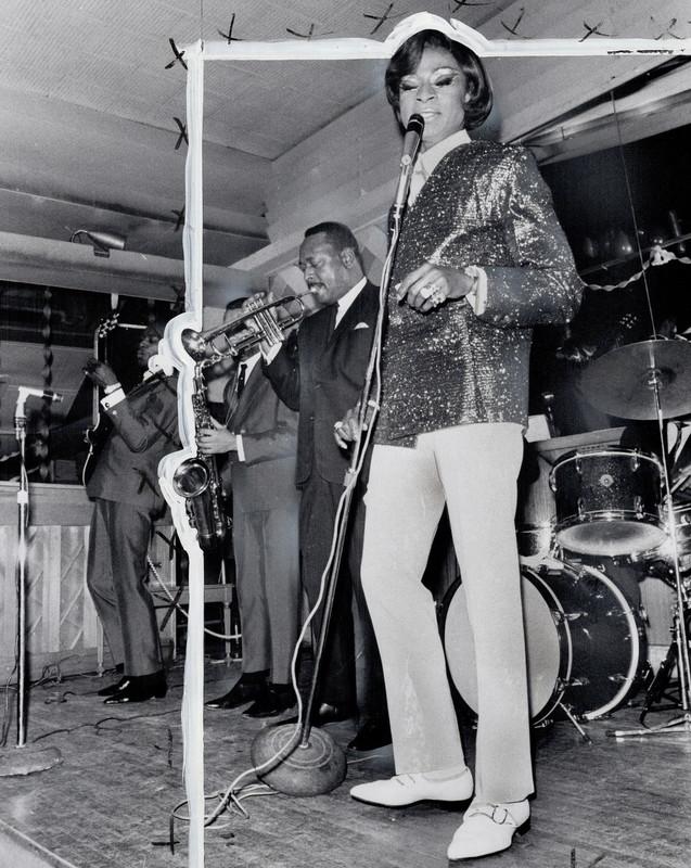 Une chanteuse portant un pantalon blanc et un blouson à paillettes tient un micro sur scène. Un saxophoniste et un trompettiste se trouvent à ses côtés. Une batterie se trouve derrière eux.