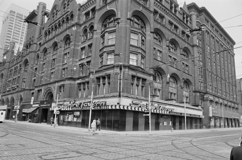 """A black and white image depicts a brick building on a corner of the street, with a bulb light across the doorway that reads """"The Saphire Tavern"""". The road is laid with streetcar tracks and wires criss-cross the air above."""