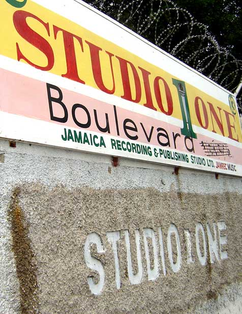 A rock inscribed with the words, in all capitals, Studio One. Above, a colourful sign reads Studio One Boulevard, Jamace Recording & Publishing Studio.