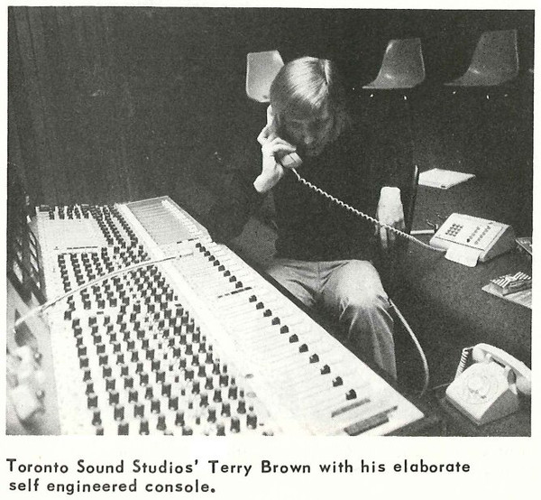 A black and white photo of a man on a landline telephone sitting in front of a large recording studio console.