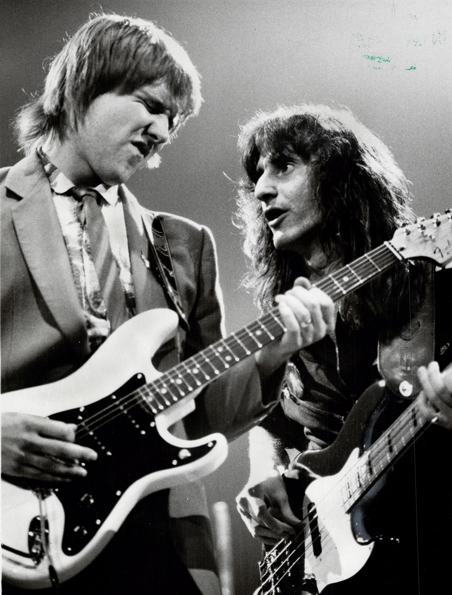 A black and white photo of Alex Lifeson and Geddy Lee playing on stage.