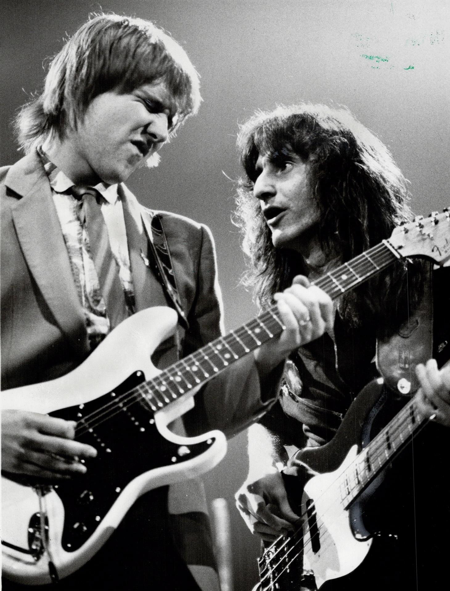 Gros plan sur deux hommes, l'un tenant une guitare et l'autre, une basse. Le guitariste a ses yeux fermés et il louche. Le bassiste le regarde intensément.