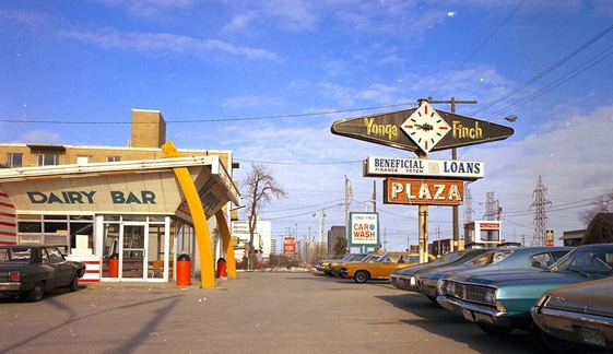 "An image of a suburban dairy bar and its parking lot from the early 1970s. A large sign features a clock with the words ""Yonge"" and ""Finch"" written on either side of it."