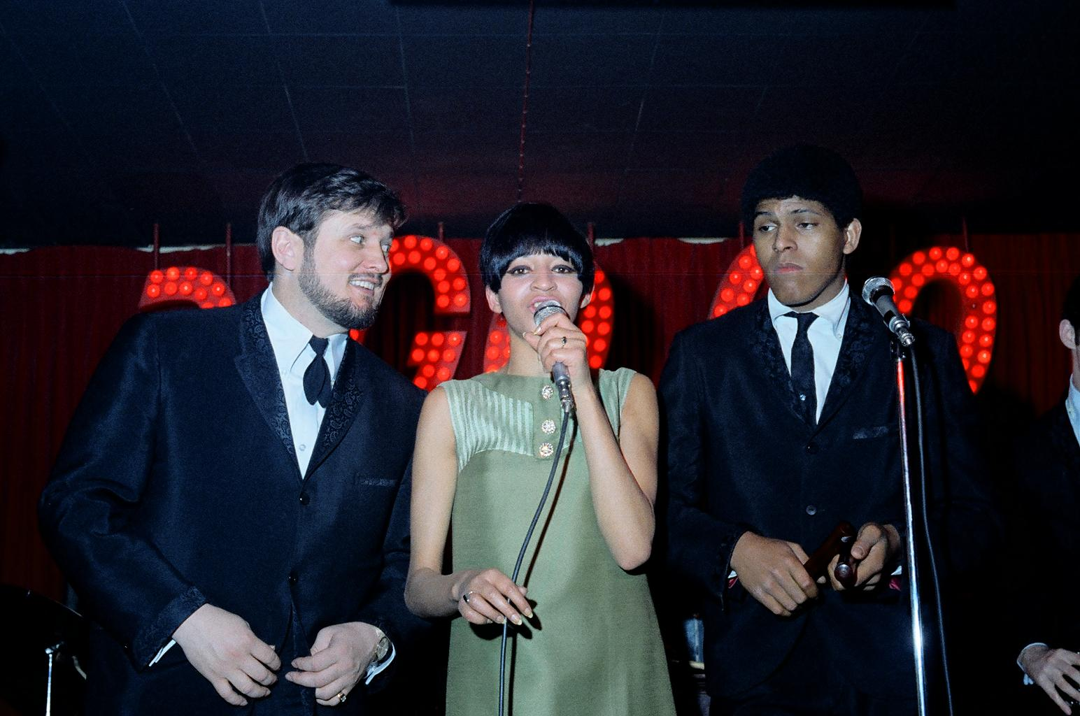 A colour photograph of three individuals, two men and a woman, performing on a stage. The men stand on either side of the woman and are dressed in black suits. The woman in the middle has a short haircut and wears a light green dress. She sings into a microphone.
