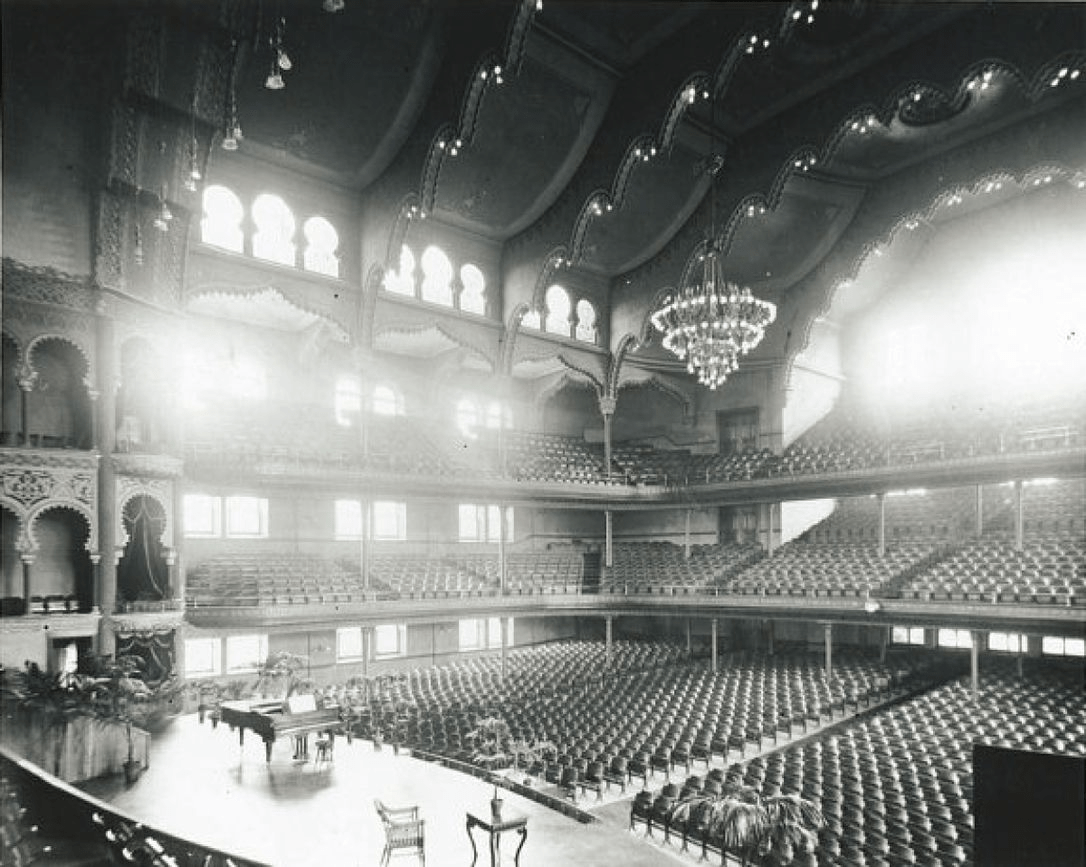 A black and white photo of the interior of a large performance space. The camera is positioned from the back of the stage so that all rows of chairs and balconies in the audience can be clearly seen. Large windows on all levels let in light to the space.