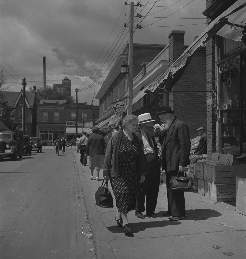 A black and white photograph showing a street scene. On the sidewalk, three people are standing. A woman walks past carrying a purse; two men are in conversation.