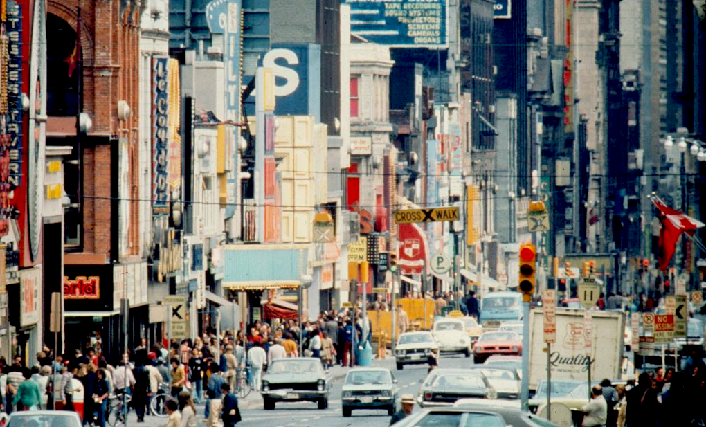 A colour photograph of a bustling street scene. The image looks directly down a busy roadway filled with cars. On either side of the street pedestrians walk in both directions.